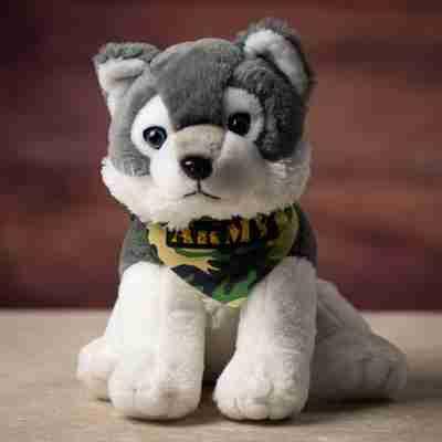 A sitting two-toned wolf wearing a camo bandanna
