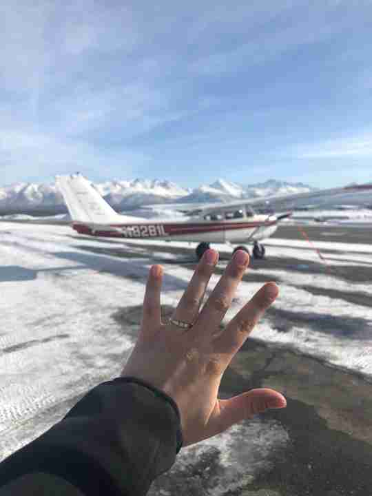 Meet Mary - showing off ring in front of snowscape and plane