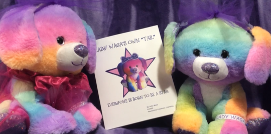 Two dressed up rainbow dogs sitting in between a book