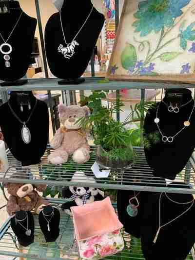 Shelves filled with plush animals, jewelry, and plants