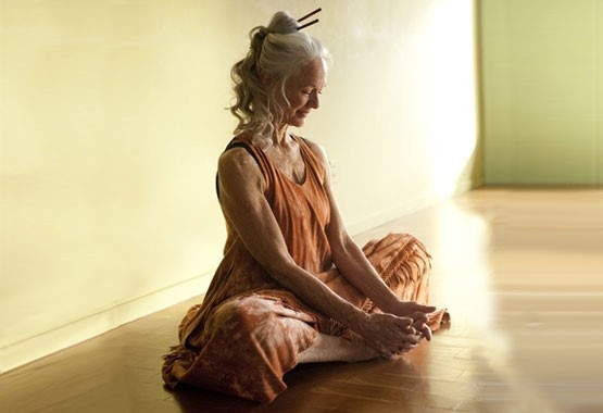A beautiful mature woman sitting in yogasana.