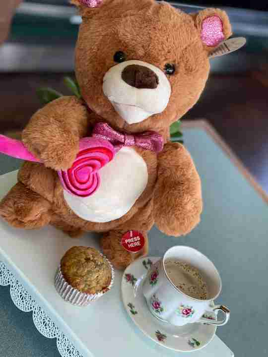 A brown bear with a next to a tea cup and a muffin
