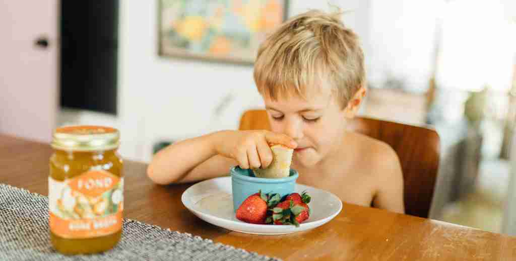 Young boy eating tomato soup and grilled cheese made with FOND bone broth