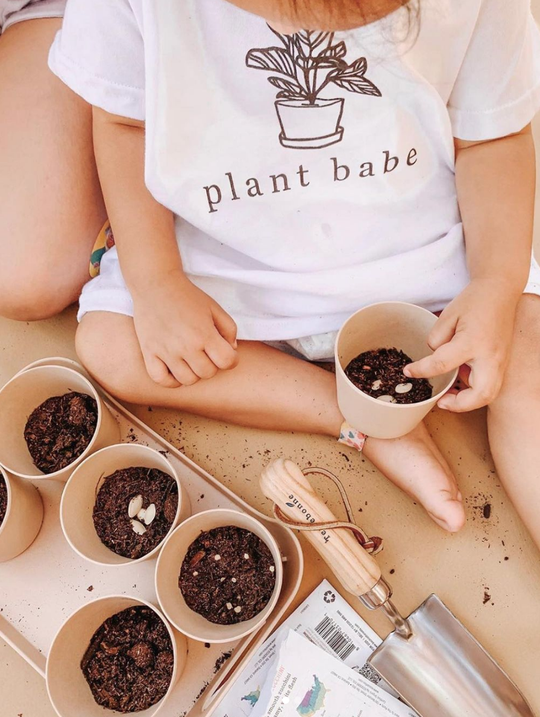 A child with gardening supplies and shirt