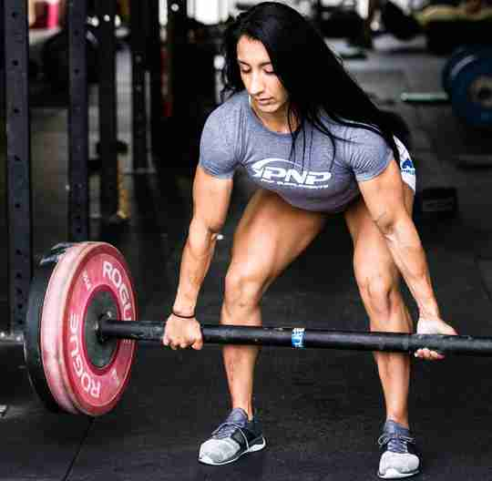 A female CrossFit athlete doing deadlifts after drinking a carbohydrate supplement drink.