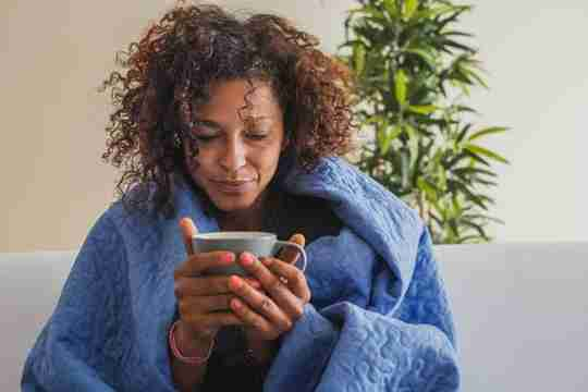 Woman in Blanket with Mug in Hand on Couch Plant
