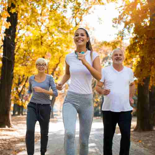 Older couple with trainer out running in park