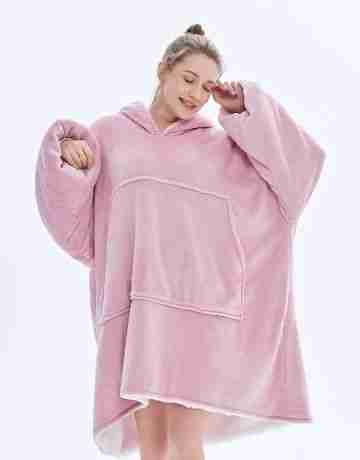 sleepy woman rubbing her eyes feeling cosy in her lotus pink Marshmallow hooded blanket for winter