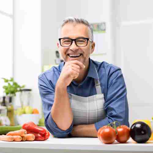 Man smiling at worktop with food