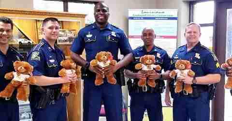 Police officers holding our teddy bears.