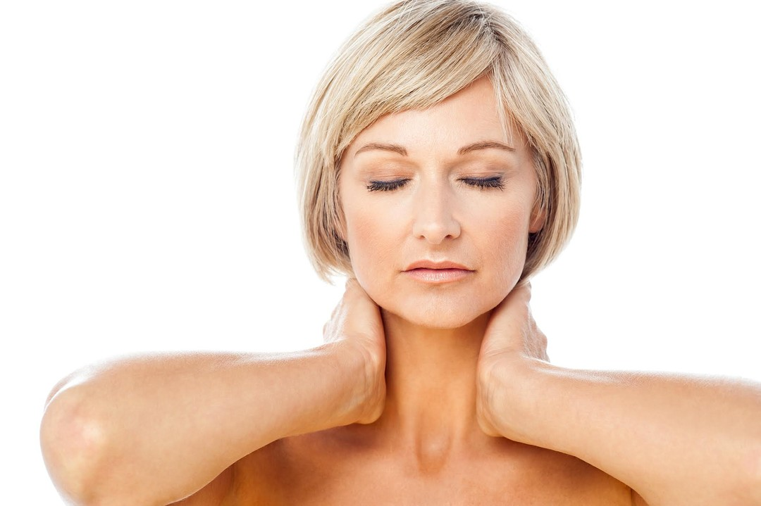a relaxed-looking woman massaging her neck