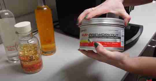 Hand Holding Preworkout Drink Fish Oil MCT Oil