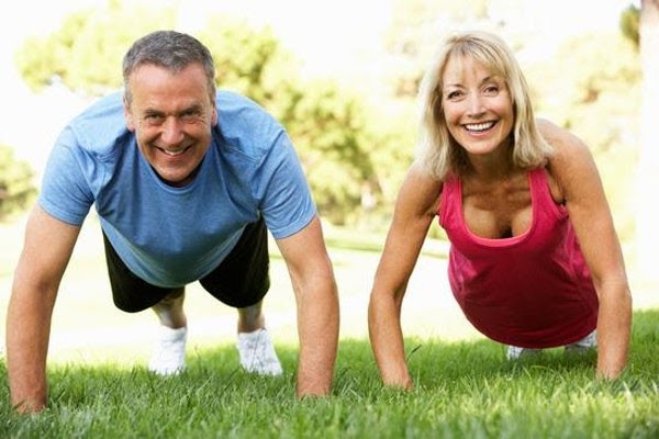 Fit Man And Woman Doing Pushups Outside in Park Smiling