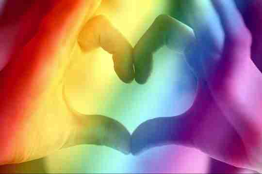 Hands making a love heart with a rainbow overlay