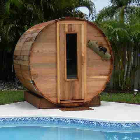 Image of an outdoor home sauna next to a pool. It is a classic barrel shape with a window door.
