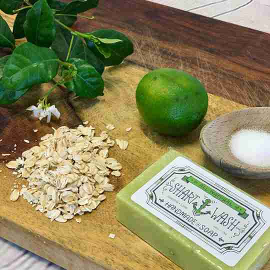 picture of a green and white jasmine flower, oatmeal, lime, sea salt and a bar of jasmine lime shart wash natural handmade soap on a wood background