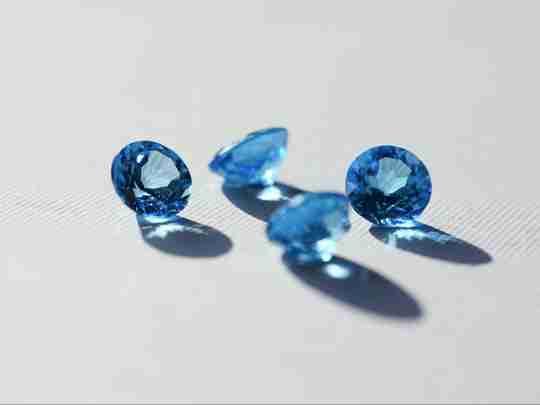 Blue Topaz gemstones on a white surface