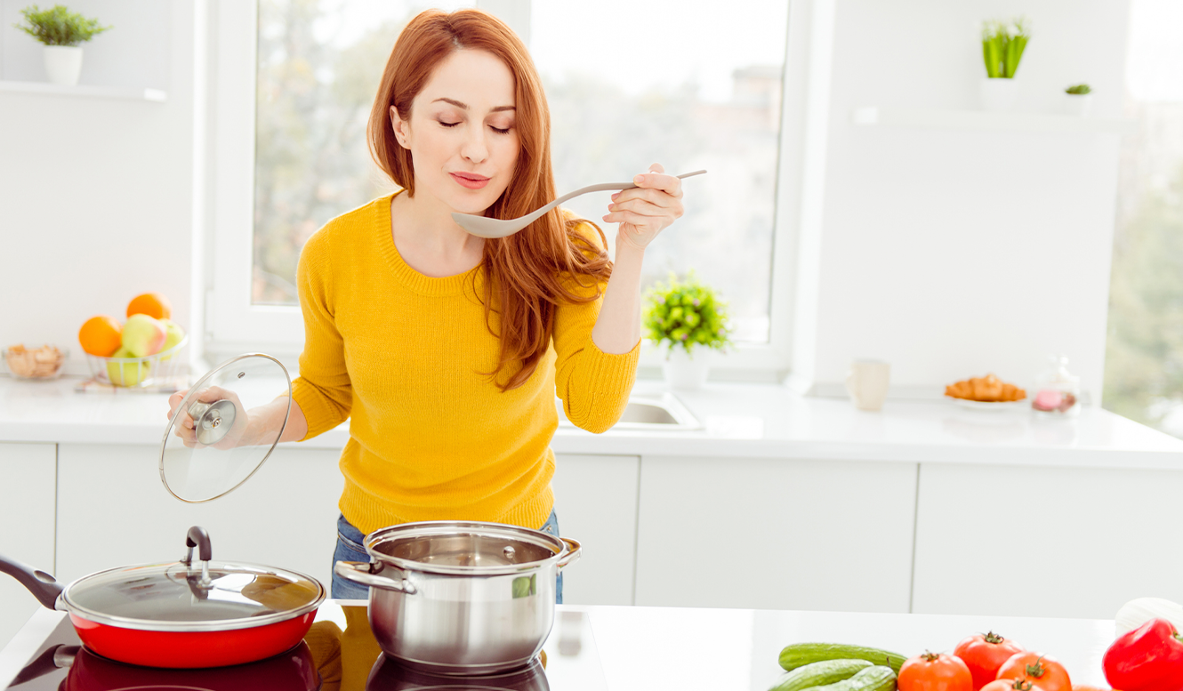a woman in the kitchen tasting soup