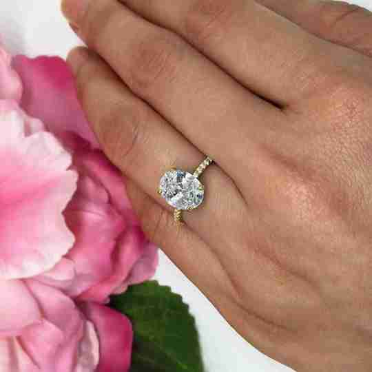 A woman wearing a cubic zirconia ring by pink flowers