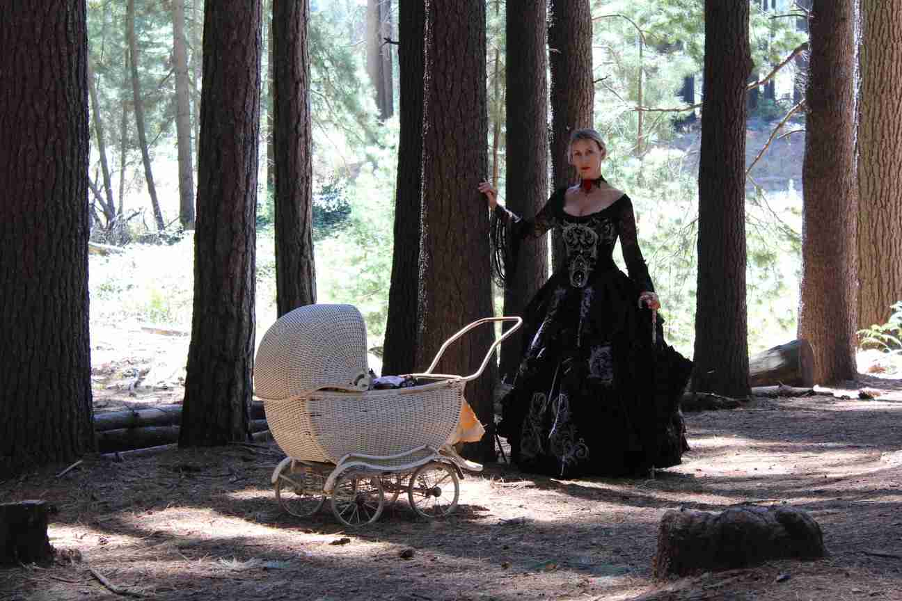 Silvia with vintage cane pram holding one of her Reborn baby dolls walking in the Sugar Pine Forest in a black gothic gown