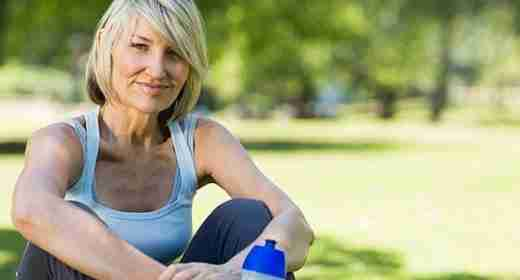 Blonde Woman in Blue Shirt Sitting Outside in Park with Water Bottle
