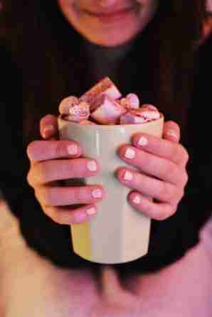 woman smiling holding a mug of hot chocolate covered with marshmallows