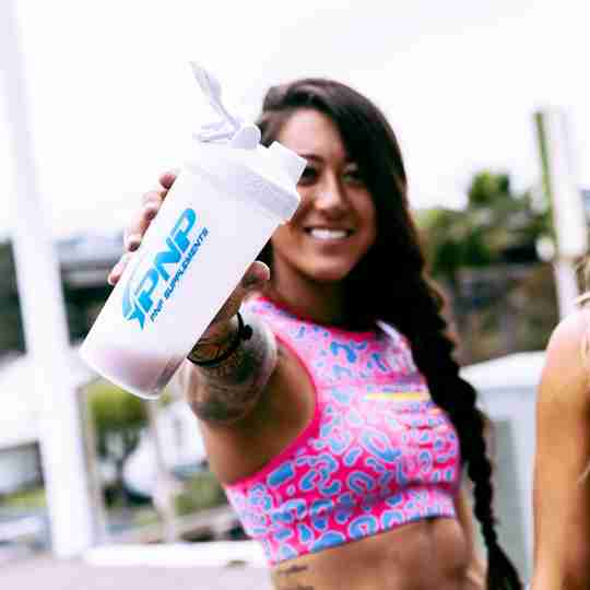 Female CrossFit athlete drinking carbohydrate supplement powder.