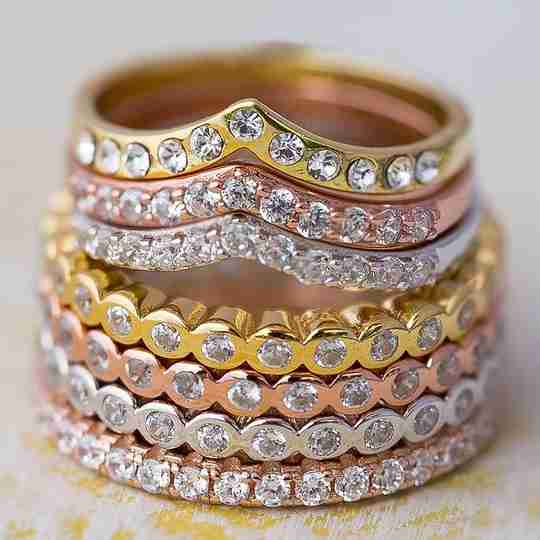 A stack of yellow gold, rose gold, and sterling silver rings