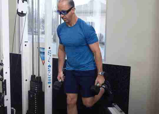 Man In Blue with Shorts Holding Dumbbells in Gym Outside View