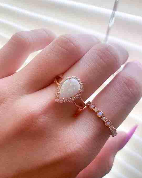 A woman wearing an opal rose gold vermeil ring
