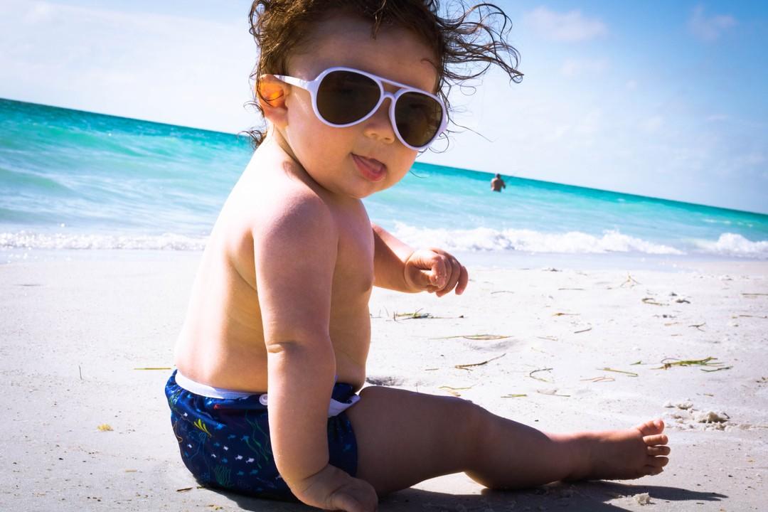 Baby in the beach wearing reusable swim diaper
