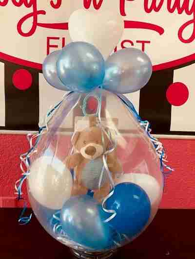 A blue and brown monkey inside a large blue balloon filled with blue and white balloons