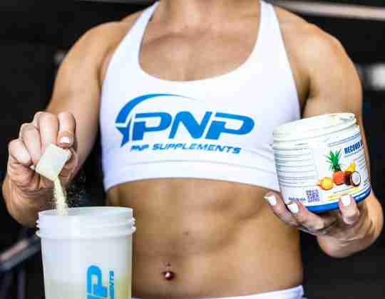 A female CrossFit athlete putting creatine in a shaker bottle for a post-workout recovery supplement drink.
