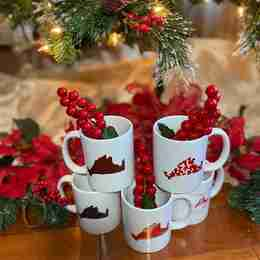 A stack of mugs under a Christmas tree
