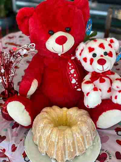 A white and red bear sitting on top of a larger red bear with a cake