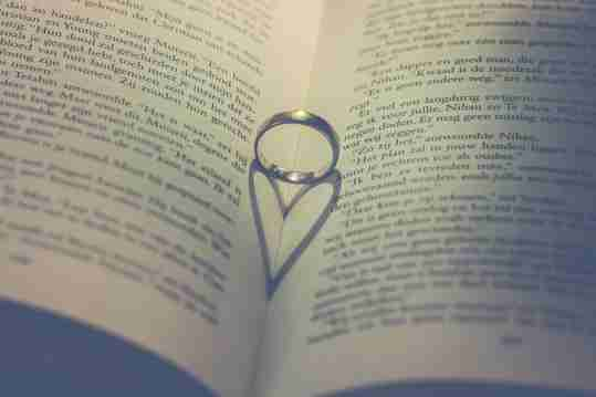 Wedding ring with love heart shadow in book