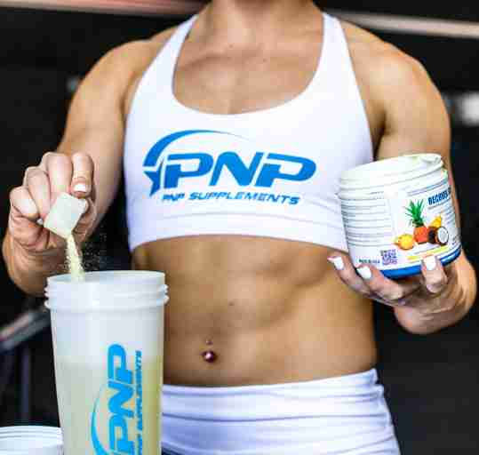 CrossFit athlete preparing a creatine supplement drink with Recover Surge by PNP Supplements.