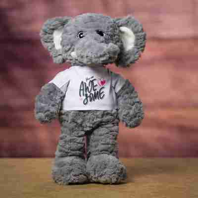 Standing gray elephant wearing a white t-shirt