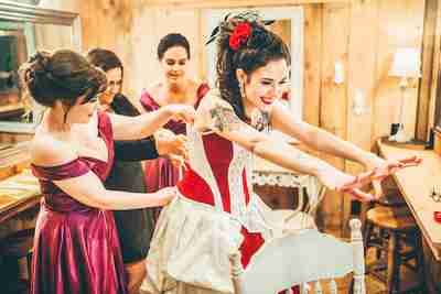 Julia being laced into her Gallery Serpentine corset gown at her Greatest Showman themed wedding