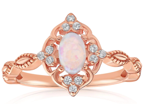 Rose gold vermeil ring with an opal center stone and a crown head with multiple gemstones surrounding the main stone