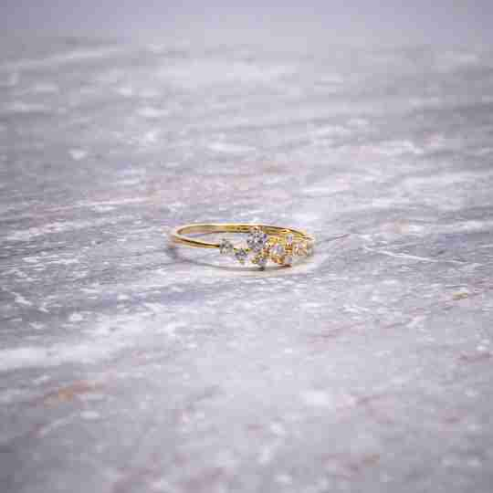 A gold vermeil ring sitting on marble
