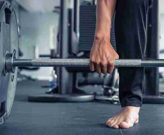 A male athlete workout barefoot with a barbell.
