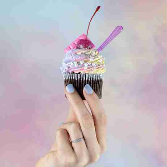 hand with Blush and Bar opal ring holding up decorated cupcake