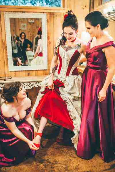 bridesmaid helps Julia get her red shoes on to match her red & ivory wedding gown made by Gallery Serpentine in Australia
