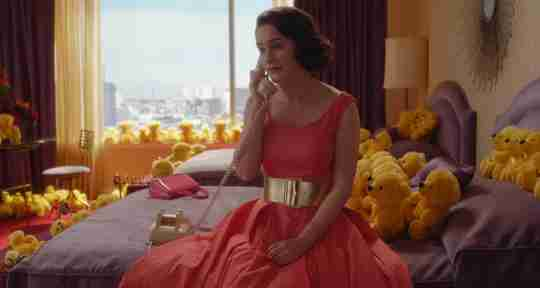 Mrs. Maisel on a bed with Yellow Colorama Bears