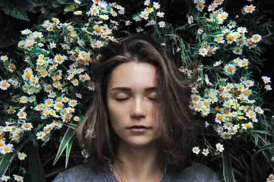 woman in field of daisies representing how diffusing essential oils over night can over stimulate the nervous system