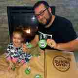 picture of a smiling dad and kid showing their dutch oven kit