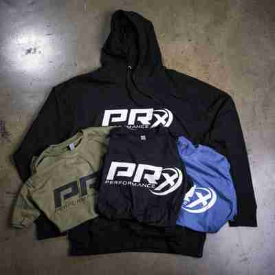 PRx black hoddie, laying on concrete with black, olive, and blue PRx t-shirts folding laying on top