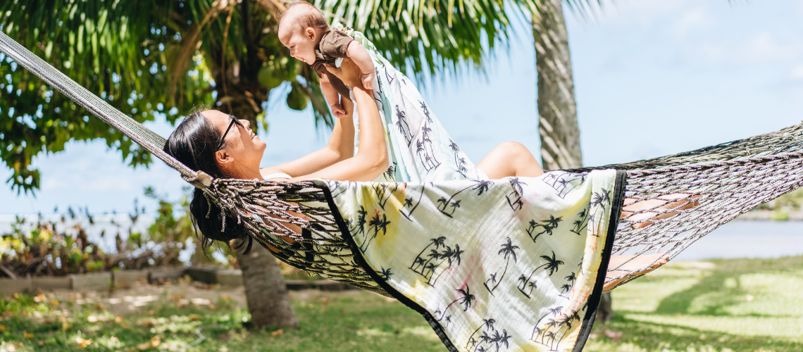 Mother and baby in hammock with Coconut Coast Baby Blankets by Coco Moon