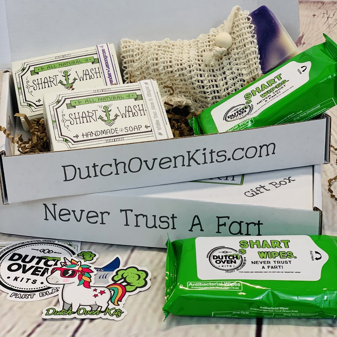 Picture of a Shart Wash Emergency Kit Gift Box open displaying a bar of lavender lemongrass soap, jasmine lime soap, 2 packs of shart wipes and a tan soap bag